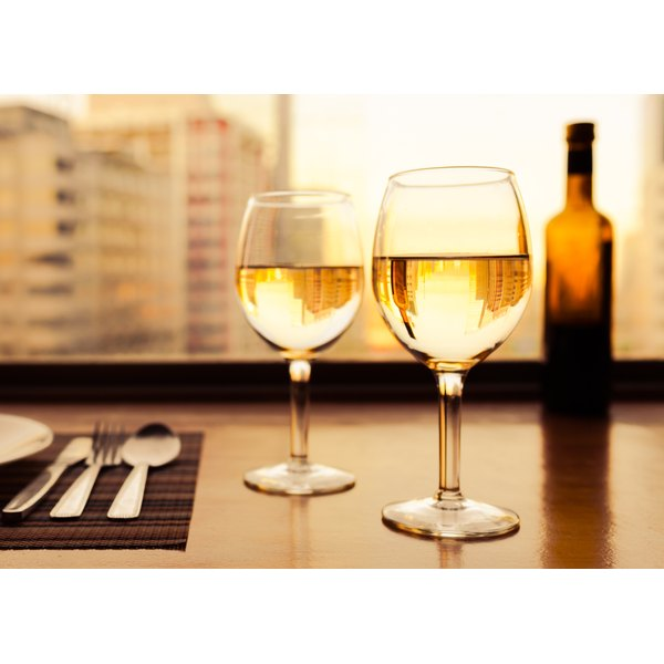 Two glasses of white wine reflecting a city skyline.