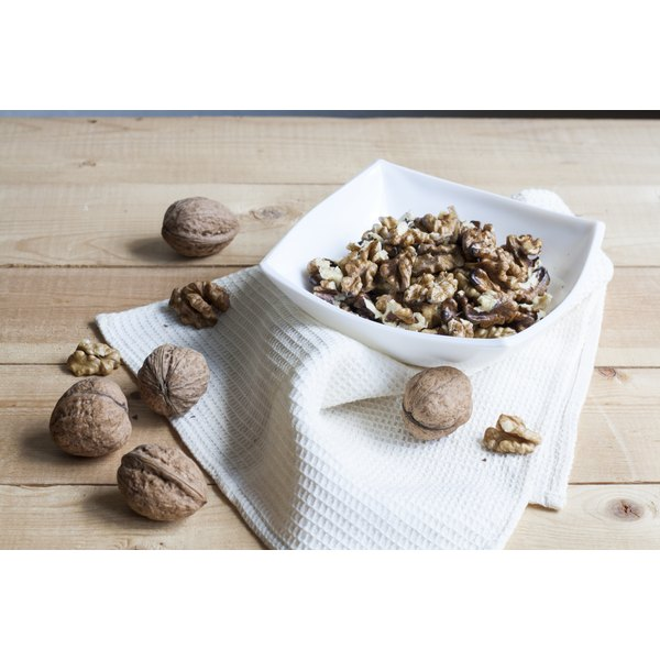 A bowl of cracked walnuts next to whole walnuts on a wood table