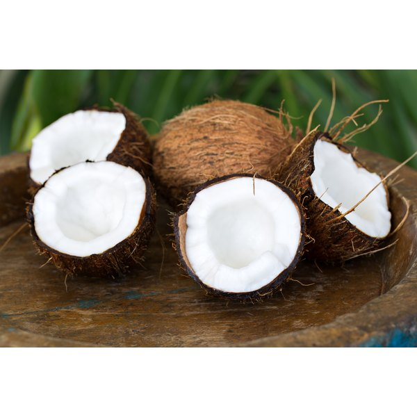 Two split coconuts on wood with a whole coconut.