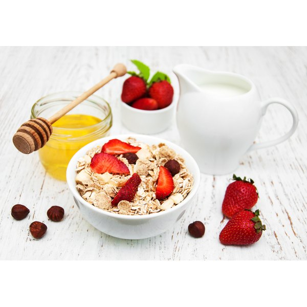 A bowl of oatmeal with fruit on it and milk, strawberries and honey sitting next to it.