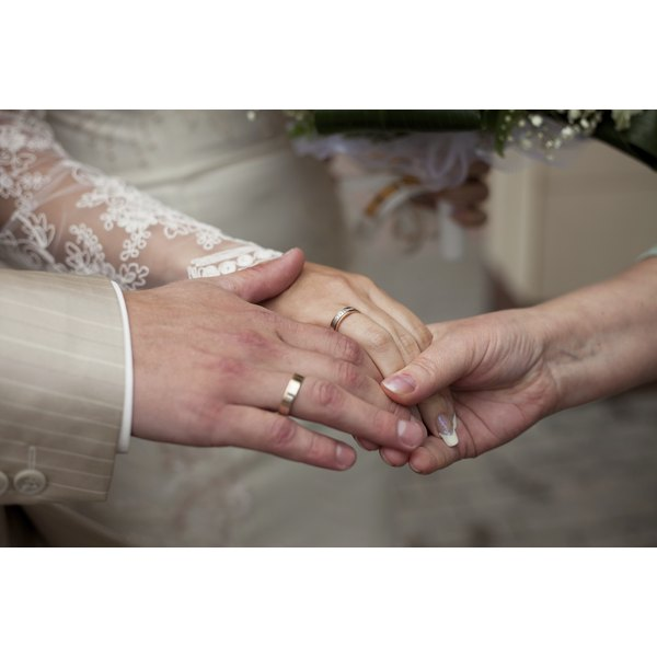 A close-up of the hands of newlyweds being blessed by another.