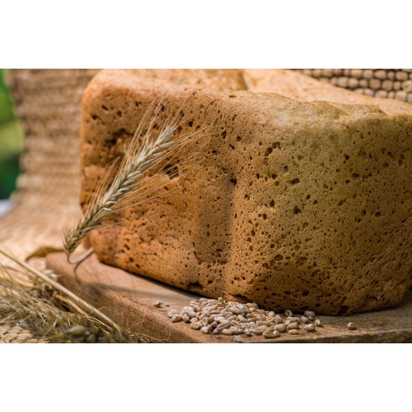 Bread made with barley flour sits on a wooden cutting board along with a stalk of barley and some barley seeds on the cutting board.