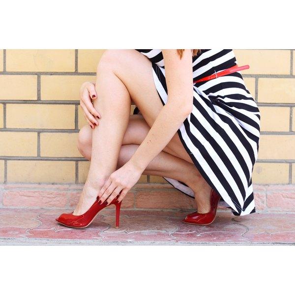 Woman in short skirt adjusting her shoe