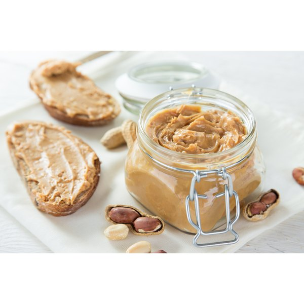A large jar of peanut butter beside two slices of toast.