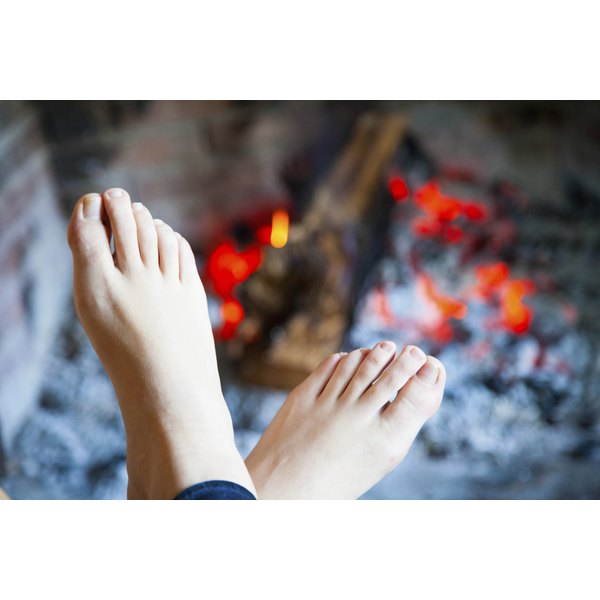 A woman warms her feet by a fire.