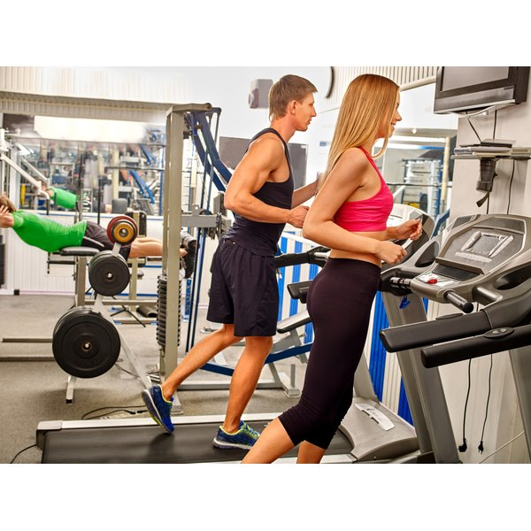A man and woman running on treadmills at a gym.