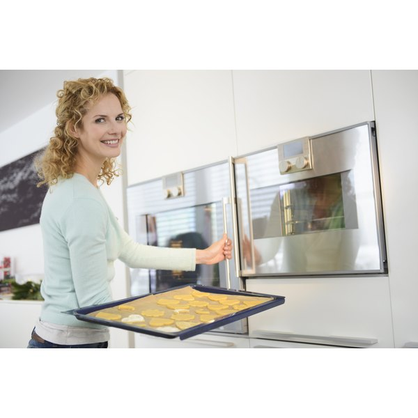 A woman about to put a tray of cookies in the oven.