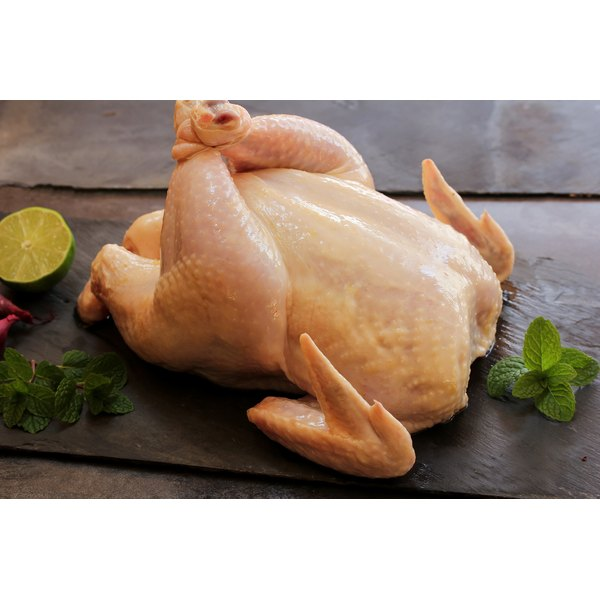 A whole chicken is ready to be roasted.