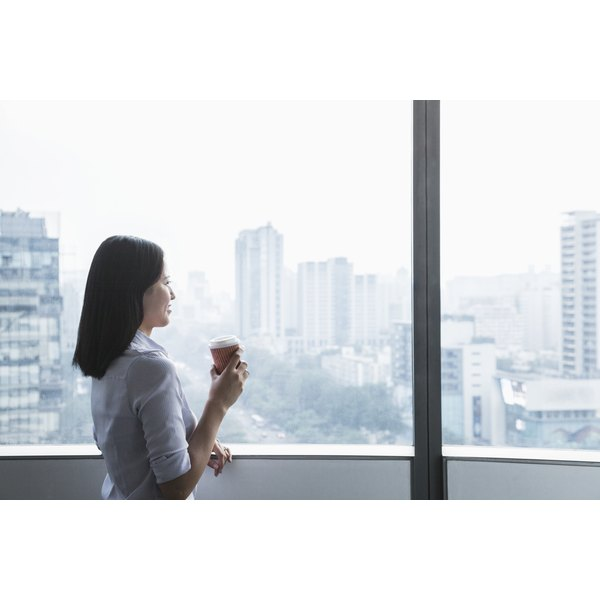 woman drinking coffee in work setting with city scape