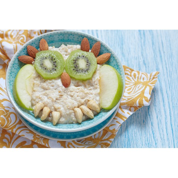 A bowl of oatmeal, fruit and nuts in the shape of an owl.