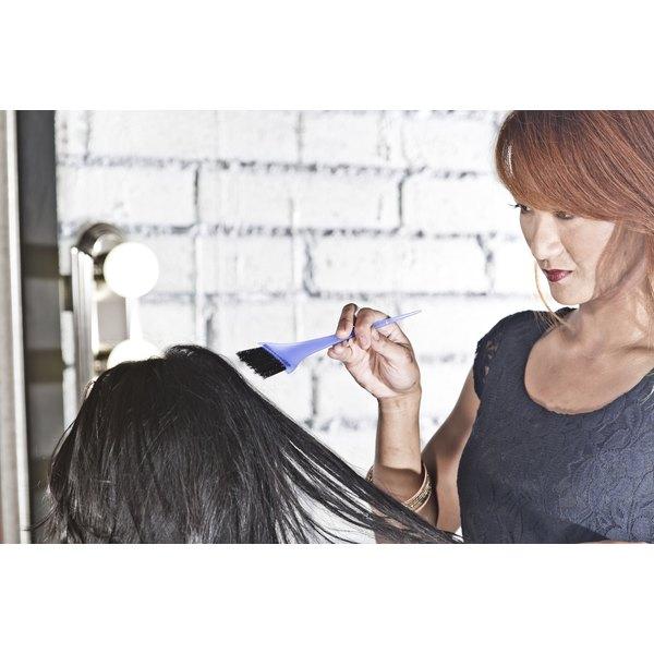 A hair dresser dying a woman's hair.