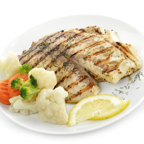 Grilled tilapia on a plate with vegetables.