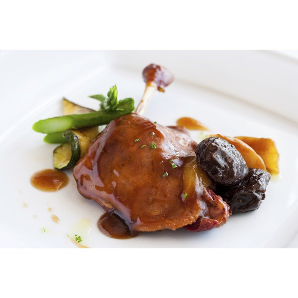 An entree of roasted goose with plum sauce.