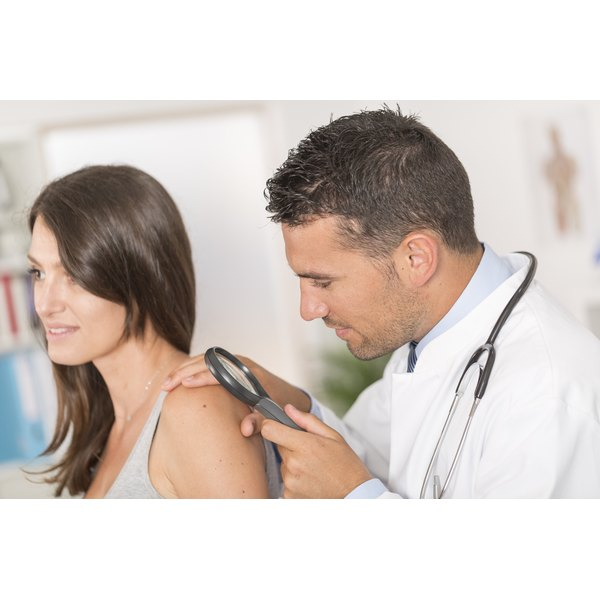 A dermatologist looking at a patients skin.