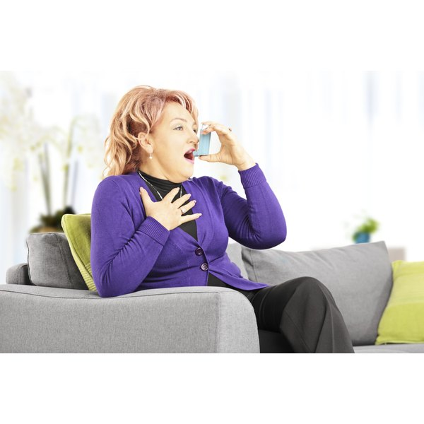 Mature woman using an inhaler to help with problems breathing