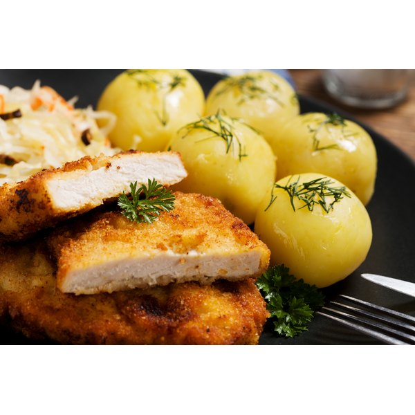 Close-up of pork chops and boiled potatoes on a plate.