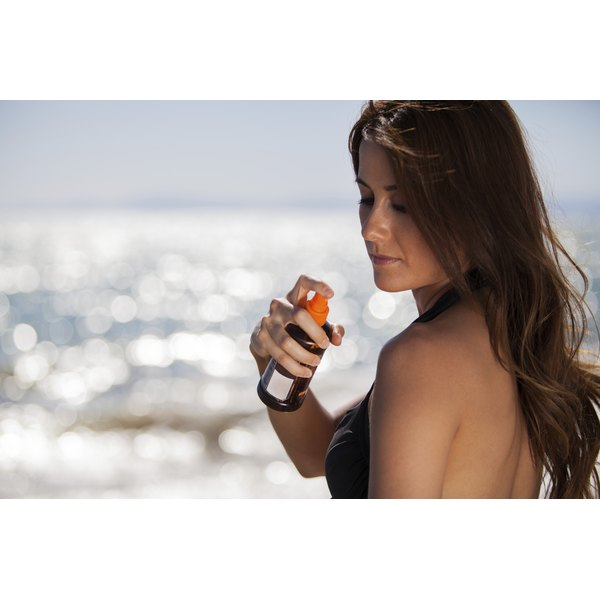 Woman spraying tanning lotion onto her shoulder at the beach.