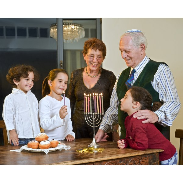 Children lighting a candle with grandparents during Hanukkah.