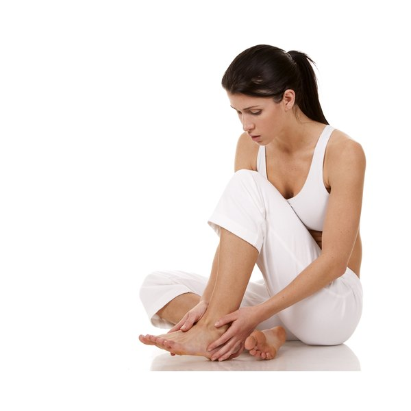 A woman holding her foot in pain.
