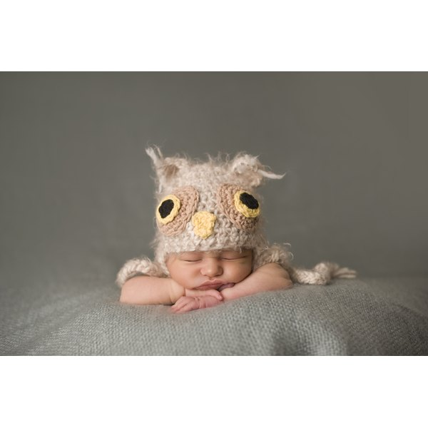 A portrait of a newborn baby wearing a knitted owl hat.
