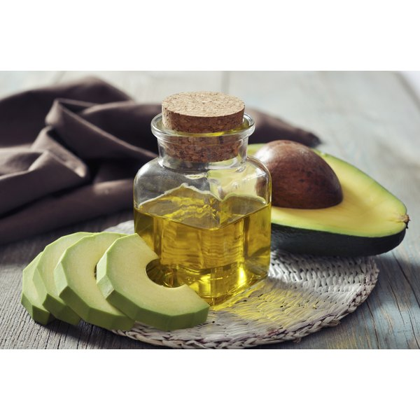 Olive oil and an avocado on a wicker trivet.
