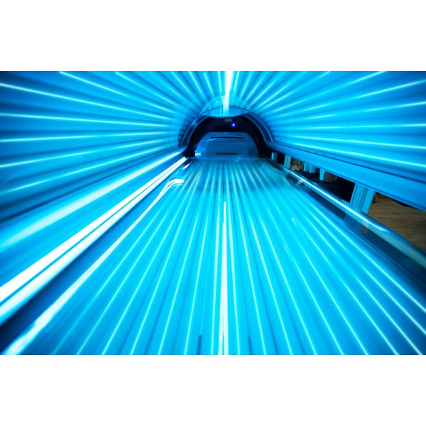 The inside of a tanning bed is seen with the lights on.