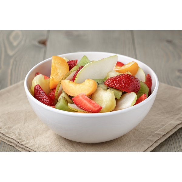 A bowl of fruit salad on a table.