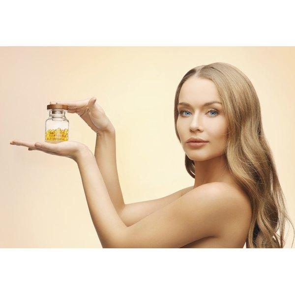 A beautiful woman holding a jar of vitamin e capsules.