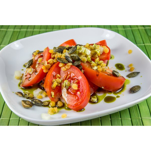 A plate of tomatoes covered in oil, vinegar and pumpkin seeds.