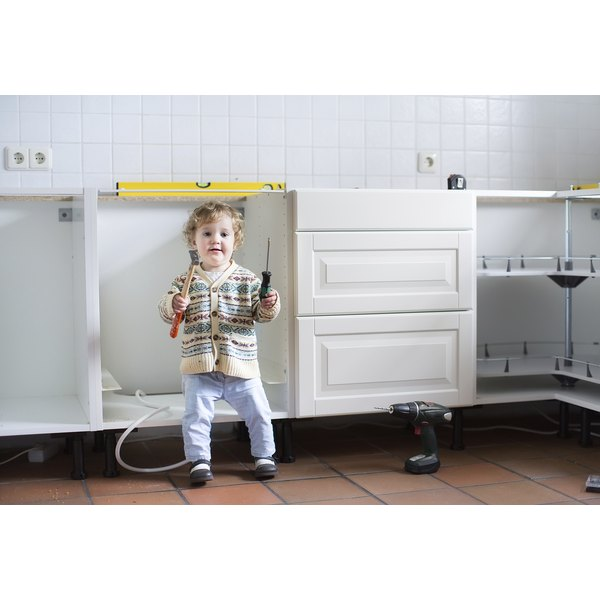 Young boy playing with tools in a kitchen.