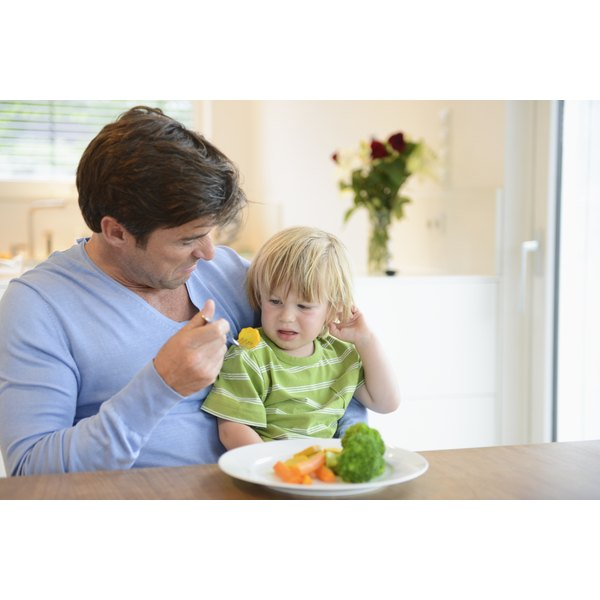 A man is feeding his son a healthy meal.