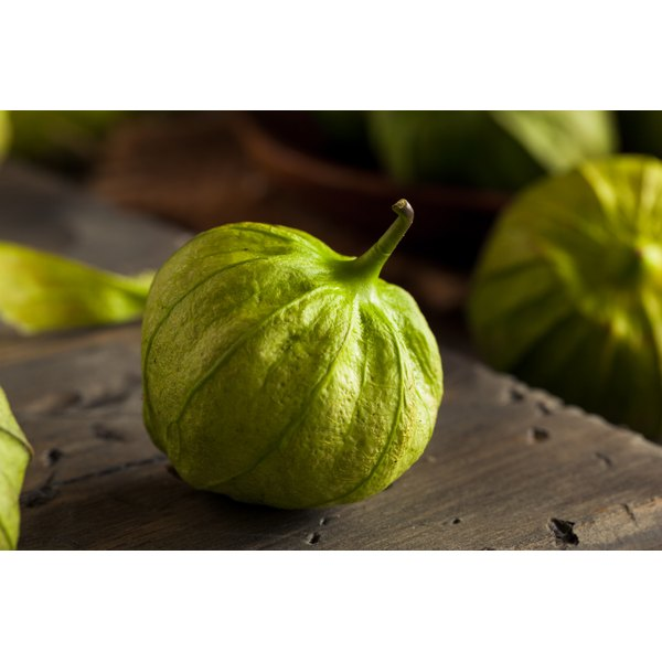 A green tomatillo on a chopping board.