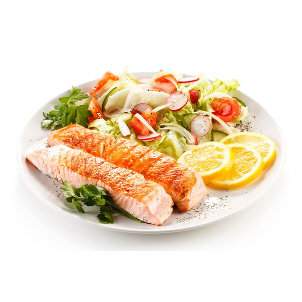 A plate with grilled salmon and vegetables sits on a white counter.