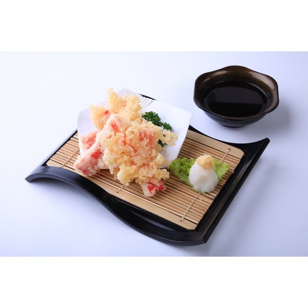 Whiting, processed into crabsticks and treated with tempura sits on a Japanese-style plate with a dish of soy sauce to the side.