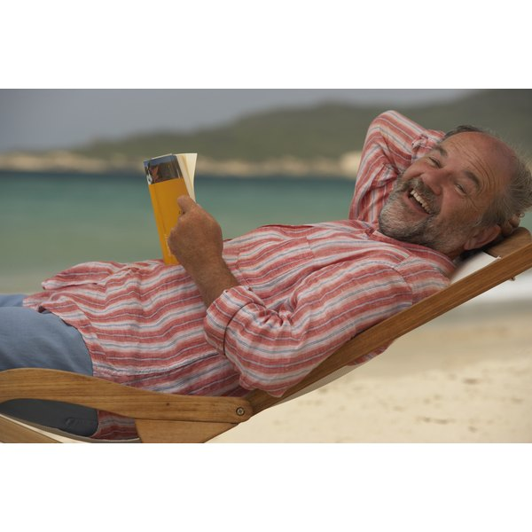 A balding middle-aged man laughs while reading a book, lounging on a beach.
