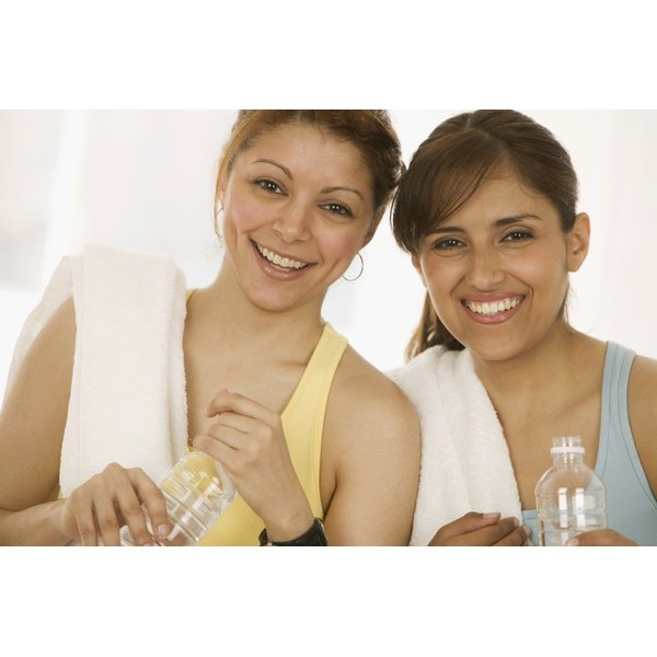 Two young women holding bottled water.