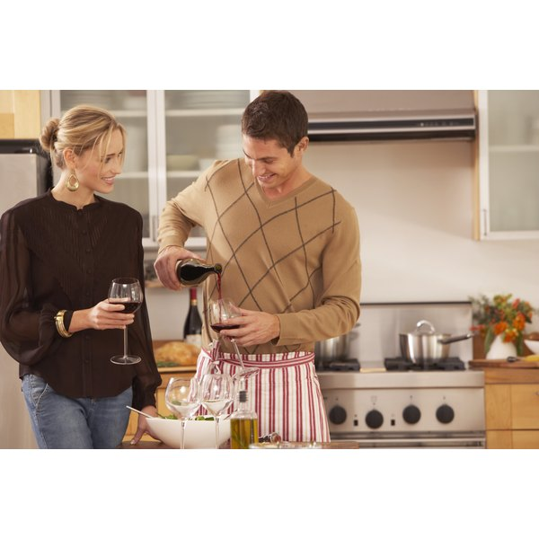 A young couple in the kitchen pouring red wine.