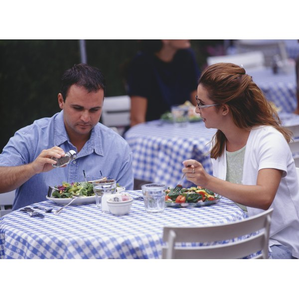 A couple eat a salad at an outdoor cafe.
