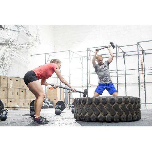A man and woman are hitting a tire.