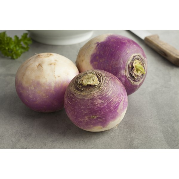 Close-up of three raw turnips on a table.