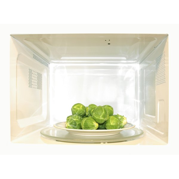 A plate of brussel sprouts inside of a microwave.