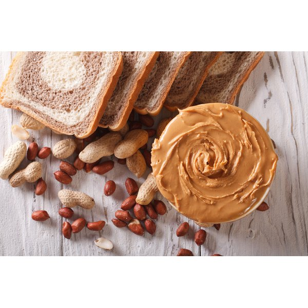 A large bar of peanut butter beside a loaf of sliced bread.