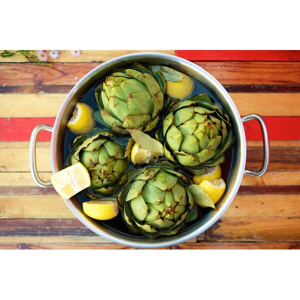 A pot of steamed or boiled artichokes with lemons.