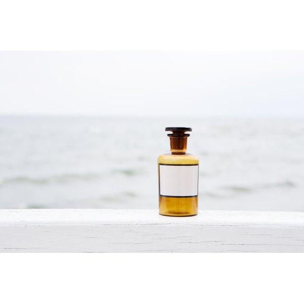 A bottle of oil sitting on a ledge with the ocean in the background.
