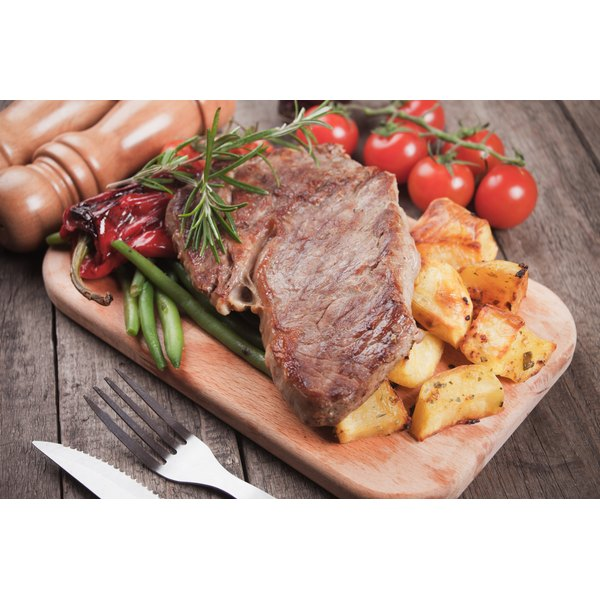 A steak sits over a bed of potatoes on a wooden cutting board.