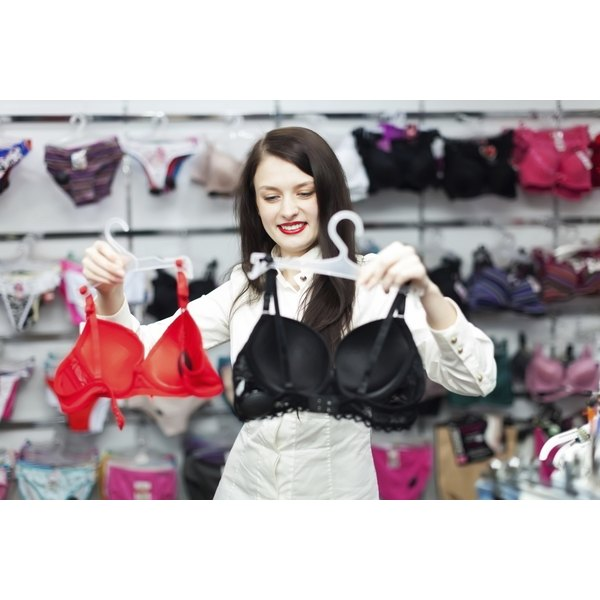 A woman holding up two bras in a store.
