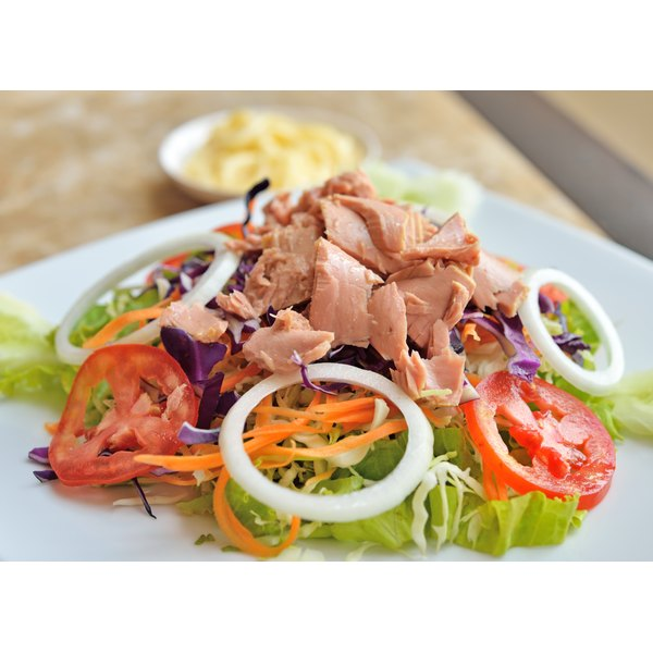 A large salad with tuna on top.