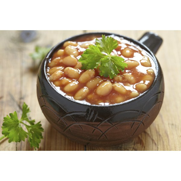 A bowl of baked beans on a wooden table.
