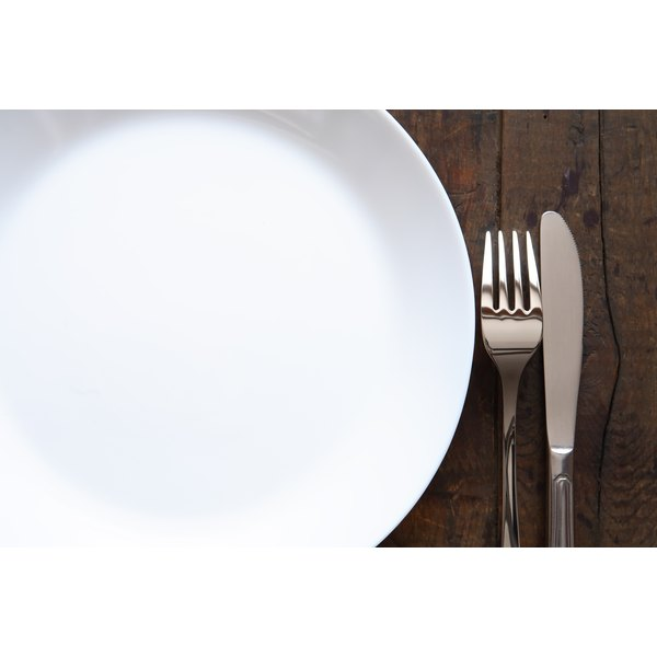 Closeup of a knife and fork next to an empty white plate.