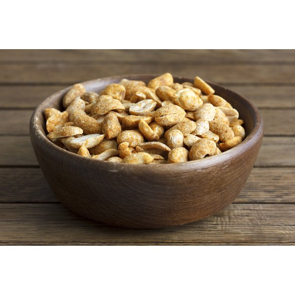 A bowl of dry roasted peanuts on a table.